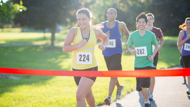 Woman crossing the finish line in a race, after working to improve 5k time