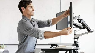 Best monitor arms: man adjusting monitor using Vari Dual monitor arm
