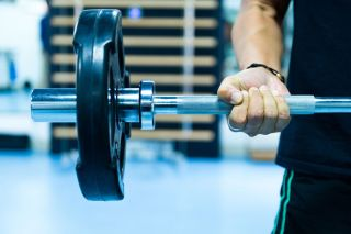 An image of a man's arm lifting a weight.