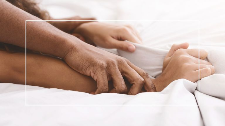 man and woman's hands holding sheets in bed