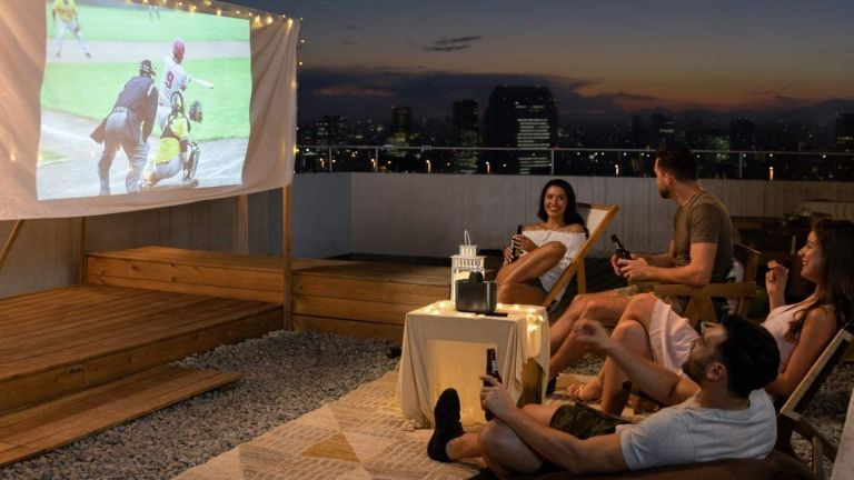 best outdoor projector: NEBULA Mars II Pro being watched from rooftop by group of friends
