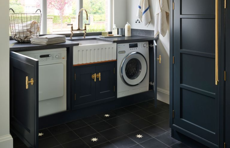 How to organize a laundry room, with black cabinetry and countertops, gold handles and faucet and a butler sink in between a washing machine and tumble dryer under a window.