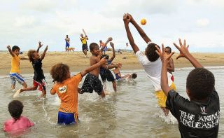 Kids play catch in the water at Mele Beach on May 16, 2012, in Port Vila, Vanuatu.