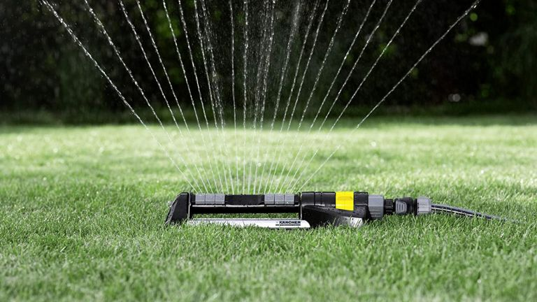 A Karcher garden sprinkler shown on a patch of lawn spraying water out at various angles