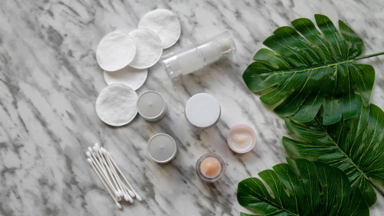 Pots of skincare with cotton buds on a marble backdrop