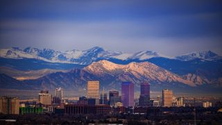 The Denver skyline with the Rocky Mountains behind it