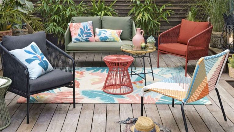 A colourful patterned outdoor rug on decking with contemporary garden furniture