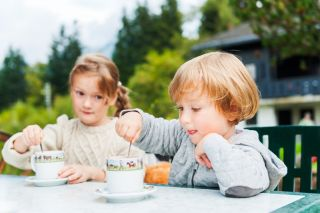 Adorable children drinking hot chocolate outdoors, spending good time on vacation in alpine mountains