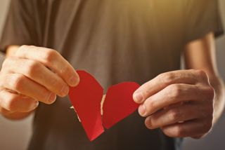 Man holding a paper heart
