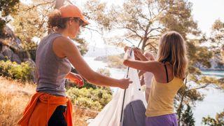 Two women taking down a tent