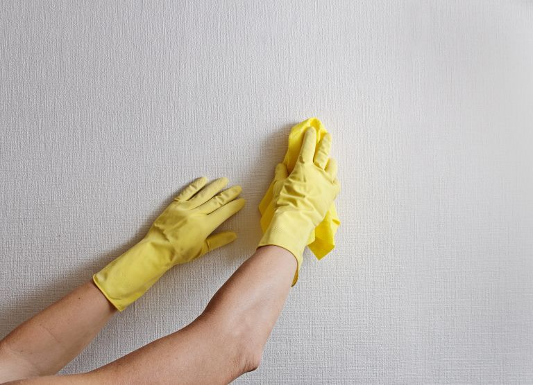Cleaning white wallpaper while wearing rubber gloves