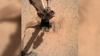 An image taken on June 3, 2020, shows the arm of the InSight lander gently pushing the heat probe into Mars.