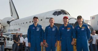 The final space shuttle crew, the astronauts of STS-135, stand with shuttle Atlantis after landing.