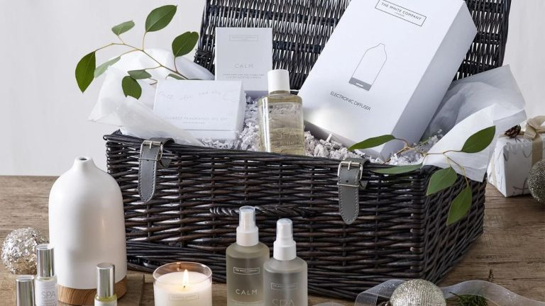 The White Company Calm Hamper in grey wicker basket with products inside and on wooden worktop