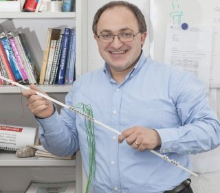 Andrea Bergamini, of Swiss Federal Laboratories for Materials Science and Technology, holds a model of an adaptable phononic crystal that could lead to much quieter consumer appliances.