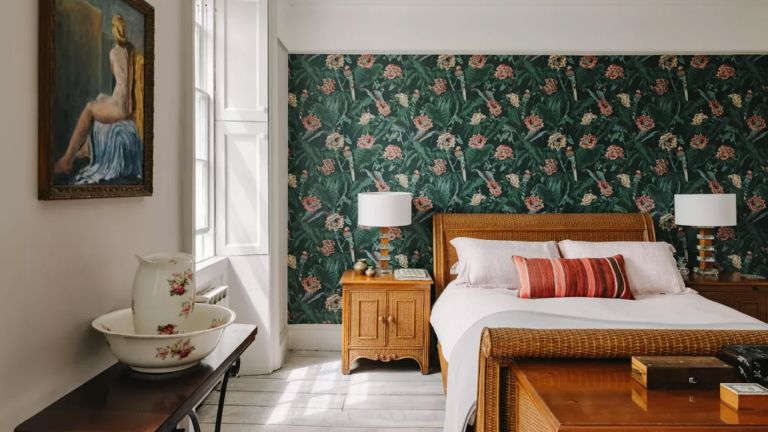 A bedroom in a historic house in bath with green floral wallpaper and a wooden bed