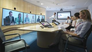 Businesspeople in meeting room taking part in video conference