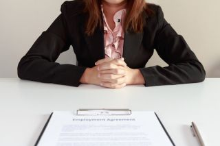 A woman sits in front of a contract with a job offer.