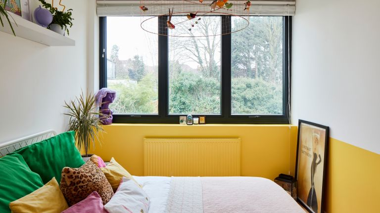 Bedroom with yellow and white colour block wall, black steel windows