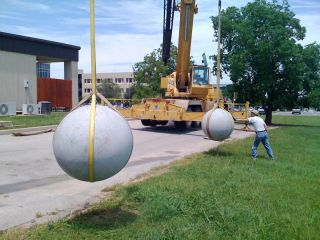 40-foot cranes suspend two granite balls, ready for impact.