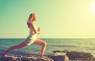 A woman does yoga near the ocean.