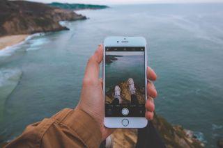 Mand med mobil sidder på klippe