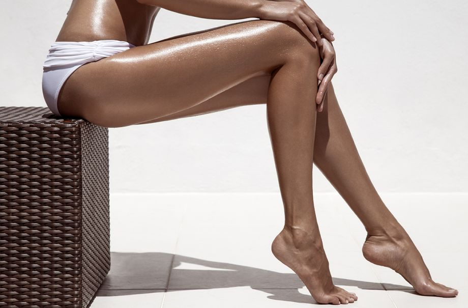 A woman with tanned legs sitting on a box.