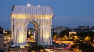 A photo of the wrapped Arc de Triomphe at night time.