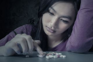 a depressed teen taking painkillers.