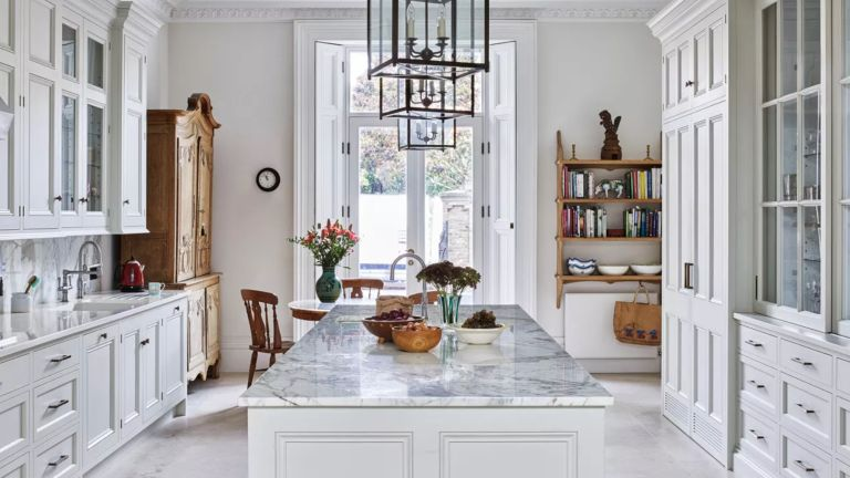 A luxury kitchen with white cabinets and marble countertops
