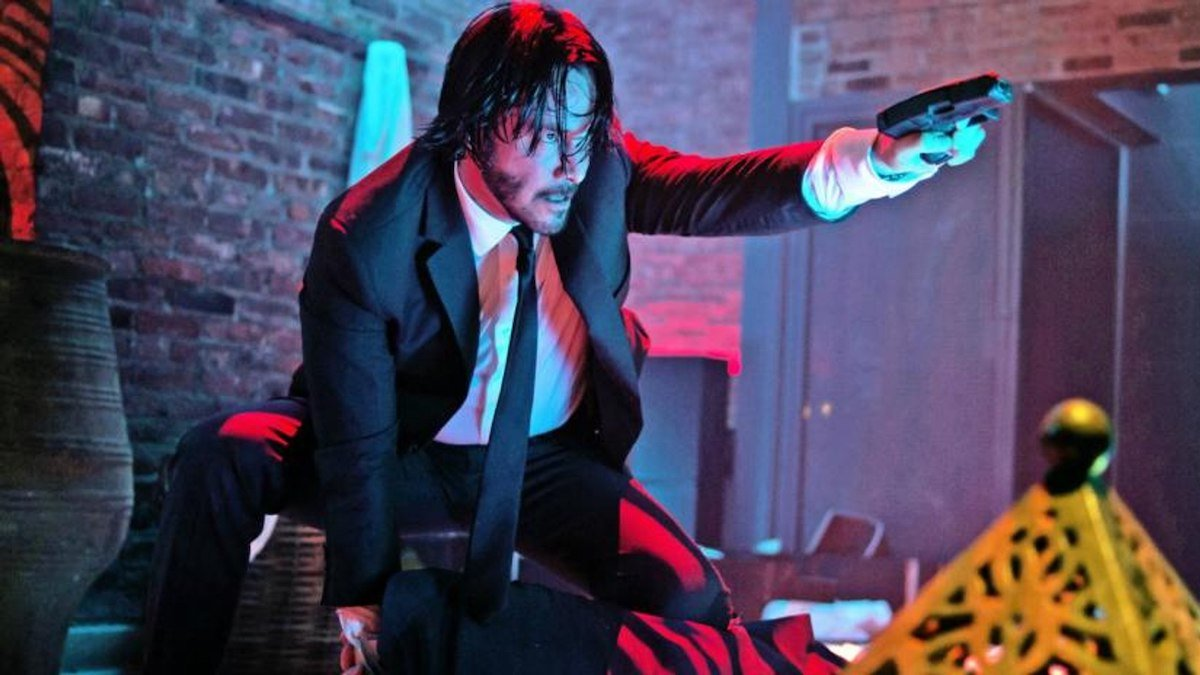 John Wick (Keanu Reeves) crouches on a table as he points a gun.