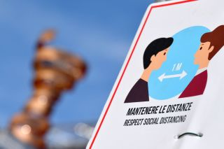 A sign at the Giro d'Italia reminding people to maintain social distancing during the COVID-19 pandemic