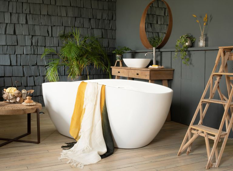 Luxury bathroom ideas White freestanding bathtub on light wooden floor with dark grey textured walls, wooden ladder and side table