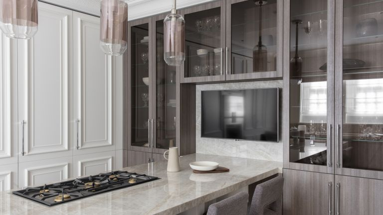 A kitchen with white cupboards and a quartzite-topped breakfast bar