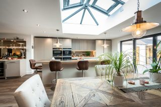 an open plan kitchen with a dining room and bar area