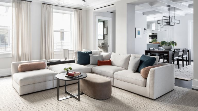 A living room with large, low corner sofa in pale grey and a partially open plan layout leading into a dining room