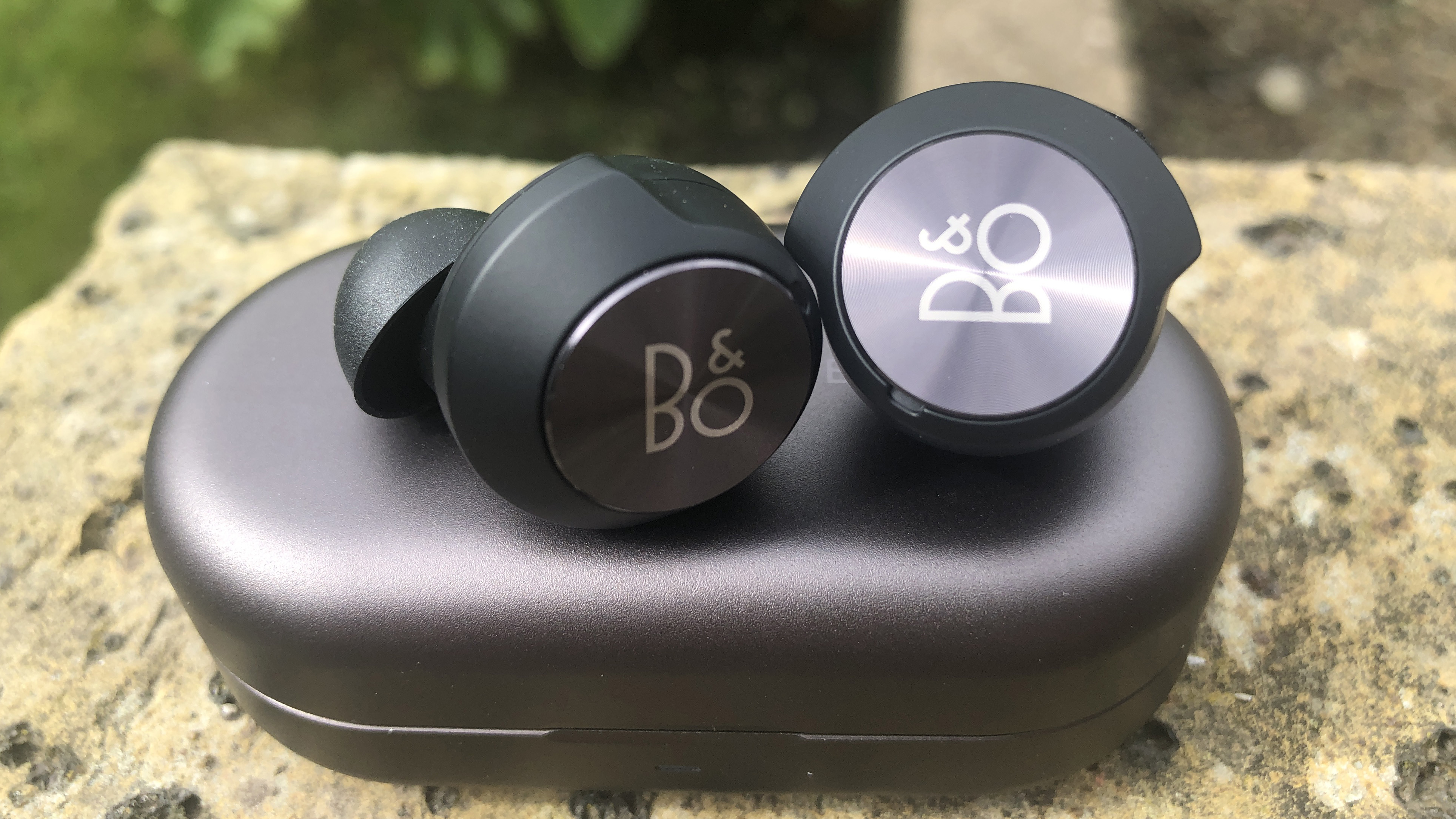 the beoplay eq true wireless earbuds on their charging case