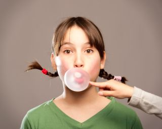 A girl blows bubbles with chewing gum