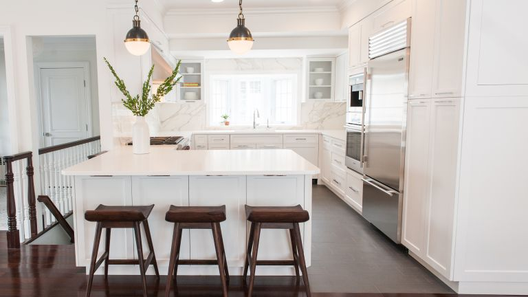 white marble kitchen with industrial pendant lights and large fridge-freezer