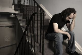 depressed guy sitting on stairs