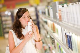 A woman smells a bottle of shampoo
