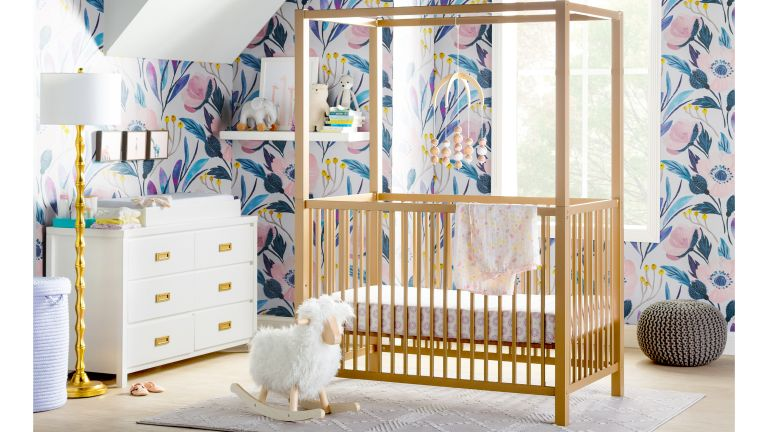 Girls nursery ideas Wooden canopy crib in nursery with printed wallpaper by Wayfair