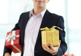 Image of businessman showing gift in his hand
