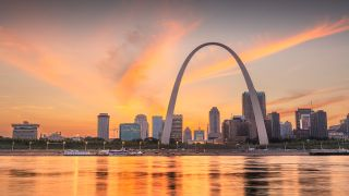 Downtown skyline of St. Louis, Missouri on the Mississippi River at dusk.