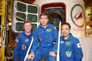 At the Baikonur Cosmodrome in Kazakhstan, NASA astronaut Mike Fossum (left), Expedition 28 flight engineer; cosmonaut and Soyuz commander Sergei Volkov (center) and Japan Aerospace Exploration Agency astronaut Satoshi Furukawa, flight engineer, pose for p