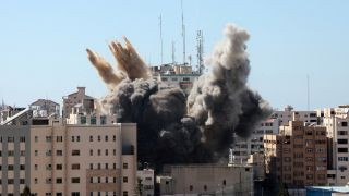 A thick column of smoke rises from the al-Jalaa tower as it is destroyed in an Israeli airstrike in Gaza city controlled by the Palestinian Hamas movement, on May 15, 2021. Israel's air force targeted the 13-floor Jala Tower housing Qatar-based Al-Jazeera television and the Associated Press news agency.