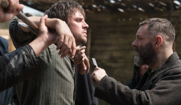 Apostle Dan Stevens restrained while Michael Sheen threatens him with a razor blade