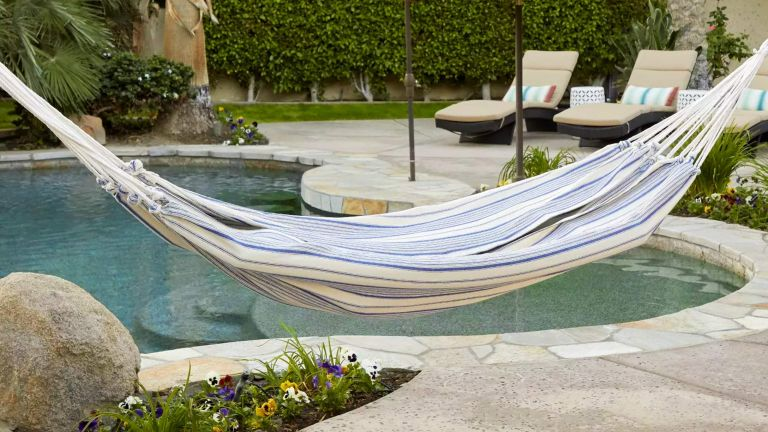A blue and white striped hammock hanging in a paved backyard by a swimming pool