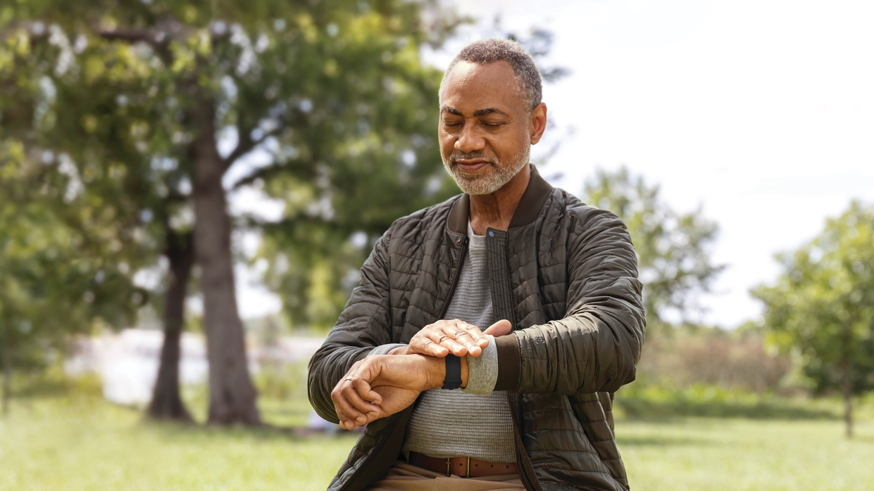 Man checking his Fitbit Sense
