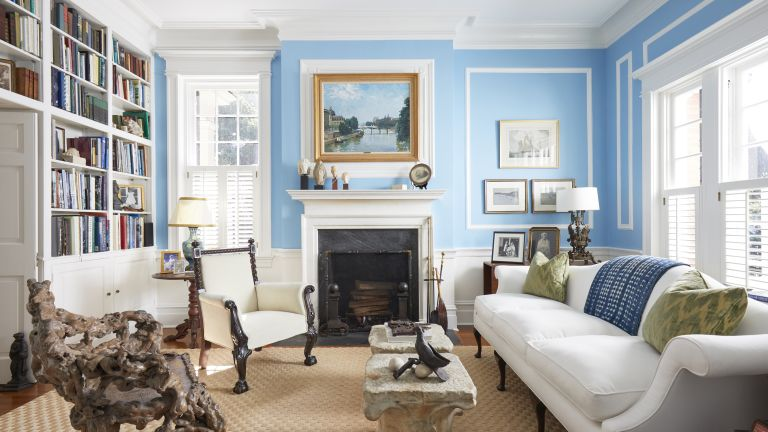 A library with light blue walls, marble fireplace and a bookcase wall